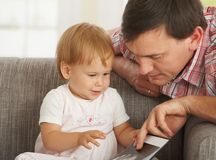 Father and toddler looking at book. On sofa at home Royalty Free Stock Image