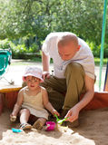 Father with  toddler   in sandbox. Dad with  toddler  playing with sand in sandbox Royalty Free Stock Photos