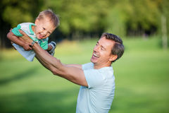 Father and toddler son having fun in park Stock Photo