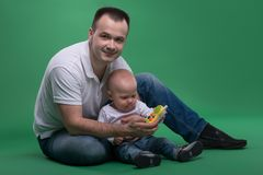 Father and toddler son playing with toy cell phone Stock Photos