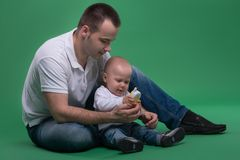 Father and toddler son playing with toy cell phone Stock Photo