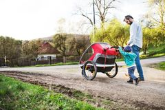 A father with toddler son pushing a jogging stroller outside in spring nature. A father with toddler son pushing a jogging stroller outside. A walk in spring Stock Images