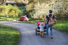 A father with toddler son pushing a jogging stroller outside in spring nature. A father with toddler son pushing a jogging stroller outside. A walk in spring royalty free stock images