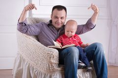 Father and toddler son sitting in armchair reading. Portrait of young handsome smiling father sitting in cozy armchair with his toddler son reading a book stock photo