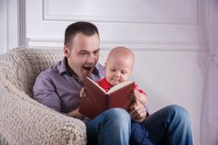 Father and toddler son sitting in armchair reading. Portrait of young handsome smiling father sitting in cozy armchair with his toddler son reading a book Royalty Free Stock Image