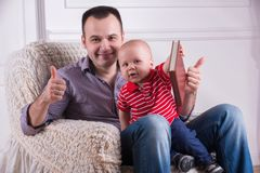 Father and toddler son sitting in armchair reading Stock Photos