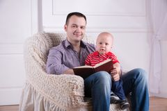 Father and toddler son sitting in armchair reading. Portrait of young handsome smiling father sitting in cozy armchair holding his toddler son on knees and Stock Image