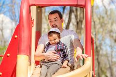 Father and toddler son sliding from children slide in the park. Child is sitting on knees of dad, father is funny and scared, kid. Father and toddler son sliding royalty free stock photos