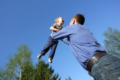Father toss up a child. Isolated on blue sky Stock Photo