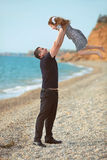 Father toss up daughter playing together on the beach carefree h Stock Photo