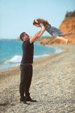 Father toss up daughter playing together on the beach carefree h Stock Photos