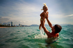 Father tosses up laughing little daughter above sea water Stock Photos