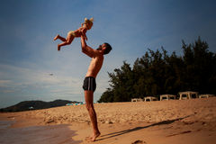 father tosses up little daughter on sand beach Royalty Free Stock Photos