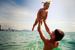 Father tosses up smiling little daughter above sea water Royalty Free Stock Photos
