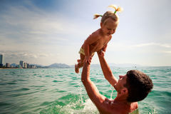 Father tosses up smiling little daughter above sea water Stock Image