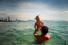 Father tosses up smiling little daughter above sea water Stock Photos