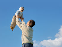 Father tossing baby. Blue sky with clouds Stock Photo