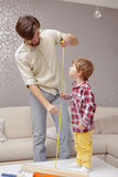 Father tracks height of his son Stock Photography