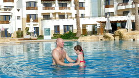 Father trains the daughter in the pool stock video footage
