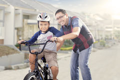 Father trains his son to ride a bicycle Stock Photo