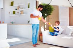 Father treats son with fresh juice and tasty dessert at summer patio garden Stock Photography