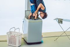 Father tries to wash his son in a washing machine standing upside down with his feet royalty free stock images