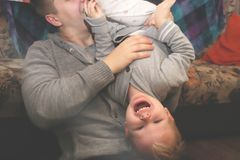 Dad and son play, indulge. The father turned his son upside down, the child laughs. The father turned his son upside down, the child laughs. Dad and son play royalty free stock photography