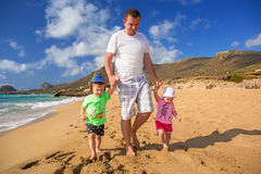 Father with twins on the beach holidays Royalty Free Stock Images