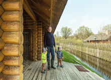 Father and twins on the threshold of wooden house Royalty Free Stock Images