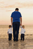 Father and twins. To the sea at sunset Royalty Free Stock Image