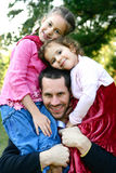 Father with two beautiful daughters. Father carrying her two beautiful young daughters on his shoulder, in the park Royalty Free Stock Images