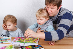 Father and two boys siblings having fun painting Royalty Free Stock Photography