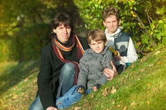 The father and two boys sit on hill slope Stock Photos