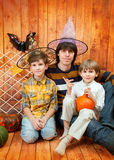 The father and two boys sit with pumpkins Royalty Free Stock Image