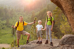 Father and two children with backpacks on beautiful nature Royalty Free Stock Images