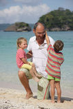 Father and two children on beach Royalty Free Stock Photo