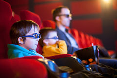 Father and two children, boys, watching cartoon movie in the cinema Stock Photos