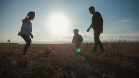 Father and two children playing in the field with soccer ball. Concept of sport.