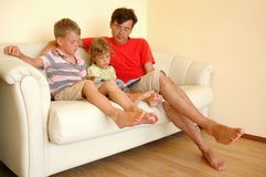 Father and two children read book. Man and two children read book sitting on sofa Royalty Free Stock Photos
