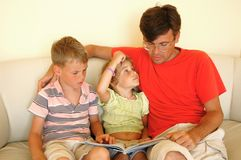 Father and two children read book. Man and two children read book sitting on sofa Royalty Free Stock Photography