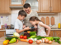 Father and two children reading cooking book and choice dishes. Happy family, girl and boy having fun with fruits and vegetables i Royalty Free Stock Photography