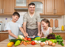 Father and two children reading cooking book and choice dishes. Happy family, girl and boy having fun with fruits and vegetables i. N home kitchen interior Stock Images