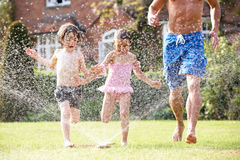 Father And Two Children Running Through Garden Royalty Free Stock Image