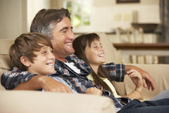 Father And Two Children Sitting On Sofa At Home Watching TV Together Stock Photo