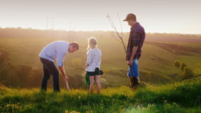 A father with two children-son and daughter together plant a tree. Picturesque background, lighting in front of the. Sunset. 4K video stock video