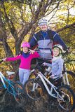 Father and two daughters on bikes in autumn royalty free stock photo