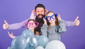 Father with two daughters having fun. Fatherhood concept. Friendly family wear funny party accessories. Fathers day stock photo