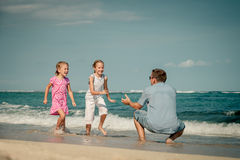 Father and two daughters running on the beach Stock Photography