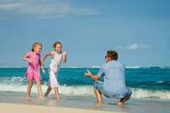 Father and two daughters running on the beach Stock Photos