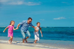 Father and two daughters running on the beach Royalty Free Stock Image